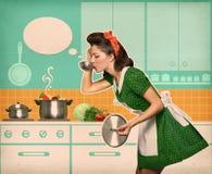 Junge Hausfrau, die ihre Suppe in der Küche mit Sprache bubb prüft stockfotografie