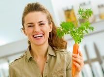 Junge Hausfrau, die Karotte in der Küche hält lizenzfreies stockbild