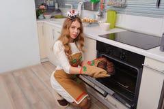 Junge Hausfrau, die kleine Kuchen vom Ofen nimmt Lizenzfreie Stockfotografie