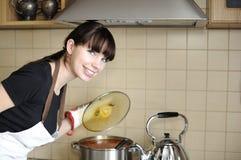 Junge Hausfrau, die Mahlzeit vorbereitet Stockfotografie