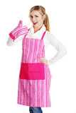 Junge Hausfrau im rosafarbenen Vorfeld, das sich Daumen zeigt Lizenzfreie Stockbilder