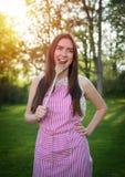 Junge Hausfrau mit Löffel in einer natürlichen Umwelt stockbild