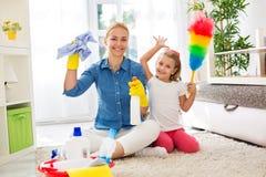 Junge Hausfraumutter und ihr Kind tun Hausarbeit zusammen Lizenzfreie Stockfotografie