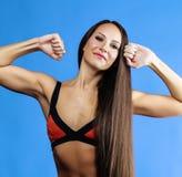 Junge hübsche Frau, die im Bikini auf Blau aufwirft Stockfoto
