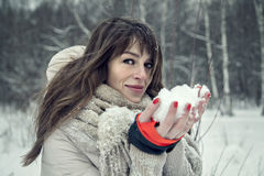 Junge hübsche Frau, die Spaß im Winterwald mit Schnee in den Händen hat Lizenzfreie Stockfotos