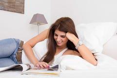 Junge hübsche Frauenlesezeitschrift, die auf dem Bett liegt Lizenzfreies Stockfoto