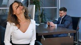 Junge healty Bürofrau, die Eignungsübung am Arbeitsplatz, beim Sitzen im Bürostuhl tut Stockbilder