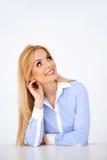Junge heiße blonde denkende und lächelnde Frau Stockfotos