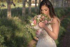 Junge herrliche Braut mit perfekter Haut und grünen den Augen, die einen Brautblumenstrauß halten Lizenzfreies Stockbild