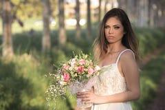 Junge herrliche Braut mit perfekter Haut und grünen den Augen, die einen Brautblumenstrauß halten Lizenzfreie Stockfotografie