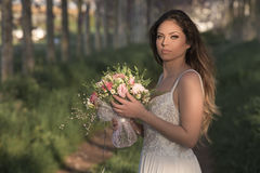 Junge herrliche Braut mit perfekter Haut und grünen den Augen, die einen Brautblumenstrauß halten Lizenzfreie Stockfotos