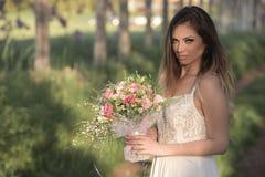 Junge herrliche Braut mit perfekter Haut und grünen den Augen, die einen Brautblumenstrauß halten Lizenzfreie Stockbilder