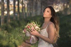 Junge herrliche Braut mit perfekter Haut und grünen den Augen, die einen Brautblumenstrauß halten Lizenzfreies Stockfoto