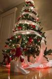 Junge herrliche Frau als Weihnachtself auf goldenem Hintergrund mit leerer Rolle Lizenzfreies Stockfoto