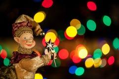 Junge herrliche Frau als Weihnachtself auf goldenem Hintergrund mit leerer Rolle Stockfoto