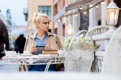 Junge herrliche Frau mit dem netten Blick, der Notenauflage hält, beim in der Kaffeestube am warmen Frühlingstag draußen sitzen, Stockfotografie