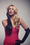 Junge herrliche kaukasische Blondine im roten Kleid Retro- Blick Stockfotografie