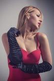 Junge herrliche kaukasische Blondine im roten Kleid Retro- Blick Stockbild
