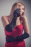 Junge herrliche kaukasische Blondine im roten Kleid Retro- Blick Lizenzfreie Stockfotografie