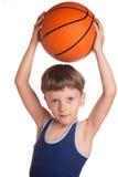 Junge hielt einen Basketballball über einem Kopf Stockbild