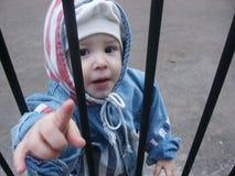 Junge hinter einem Gitter lizenzfreies stockfoto