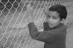 Junge hinter Zaun Stockbild