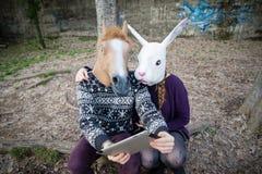 Junge Hippie cuople Pferde- und Kaninchenmaske unter Verwendung der Tablette Stockfotografie
