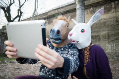 Junge Hippie cuople Pferde- und Kaninchenmaske unter Verwendung der Tablette Stockfotos