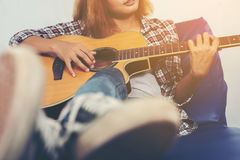 Junge Hippie-Frau, die eine Gitarre spielt Lizenzfreies Stockfoto