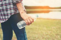 junge Hippie-Frau, die Flasche Wasser am Sommergrünpark hält Stockfotos