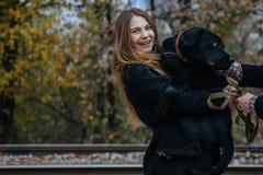 Junge Hippie-Frau, die Spaß mit ihrem Hund hat stockfotografie