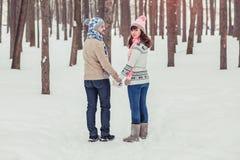 Junge Hippie-Paare, die einen Weg im Winterwald haben Lizenzfreies Stockfoto