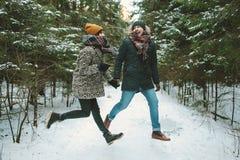 Junge Hippie-Paare, die in Winterwald springen Lizenzfreie Stockbilder