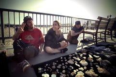 Junge Hippieleute, die Edelsteinsteine auf der Straße nah an dem Strand verkaufen lizenzfreies stockbild