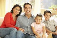 Junge hispanische Familie, die auf Sofa At Home sich entspannt Lizenzfreie Stockfotos