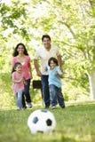 Junge hispanische Familie, die Fußball im Park spielt Lizenzfreie Stockfotografie