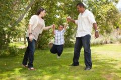 Junge hispanische Familie, die Spaß im Park hat Lizenzfreie Stockfotografie