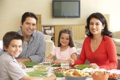 Junge hispanische Familie, die zu Hause Mahlzeit genießt lizenzfreie stockbilder