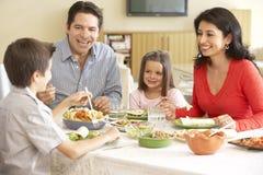 Junge hispanische Familie, die zu Hause Mahlzeit genießt stockbilder