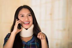 Junge hispanische Frau des Headshot, welche die tragende Halsklammer, glücklich lächelnd bei der Unterhaltung am Telefon, Verletz Lizenzfreie Stockfotos