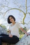Junge hispanische Frau, die in einem Baum sitzt Stockbilder