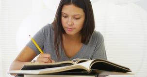 Junge hispanische Frau, die Forschung auf Schreibtisch tut Stockfotos