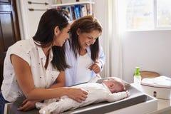 Junge hispanische Großmutter und erwachsene Tochter, die mit ihrem Babysohn auf ändernder Tabelle, Taille oben spielt lizenzfreie stockfotos