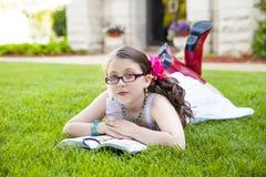 Junge hispanische Mädchen-Lesung draußen Stockfotografie