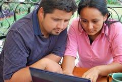 Junge hispanische Paare mit Laptop Stockfotos