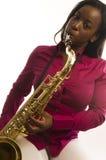 Junge hispanische schwarze Frau, die Beschaffenheit-Saxophon spielt Stockfotografie
