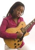 Junge hispanische schwarze Frau, die elektrische Gitarre spielt Lizenzfreie Stockfotografie