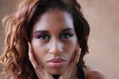 Junge hispanische schwarze Frau, die ihr Gesicht in ihren Händen höhlt Stockbild