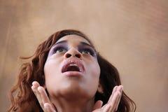 Junge hispanische schwarze Frau, die oben schaut Stockbild