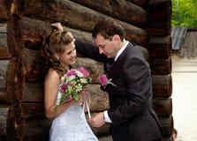 Junge Hochzeitspaare alleine nahe hölzernem Haus stockbilder